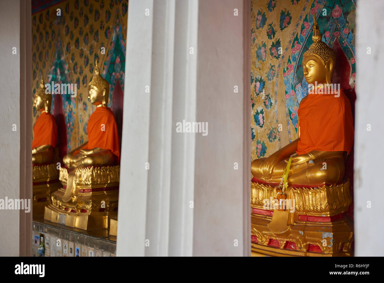Three of the several golden Buddha statues lined up in a diminishing perspective under the cover of one of the Ordination Hall in Bangkok, Thailand. Stock Photo