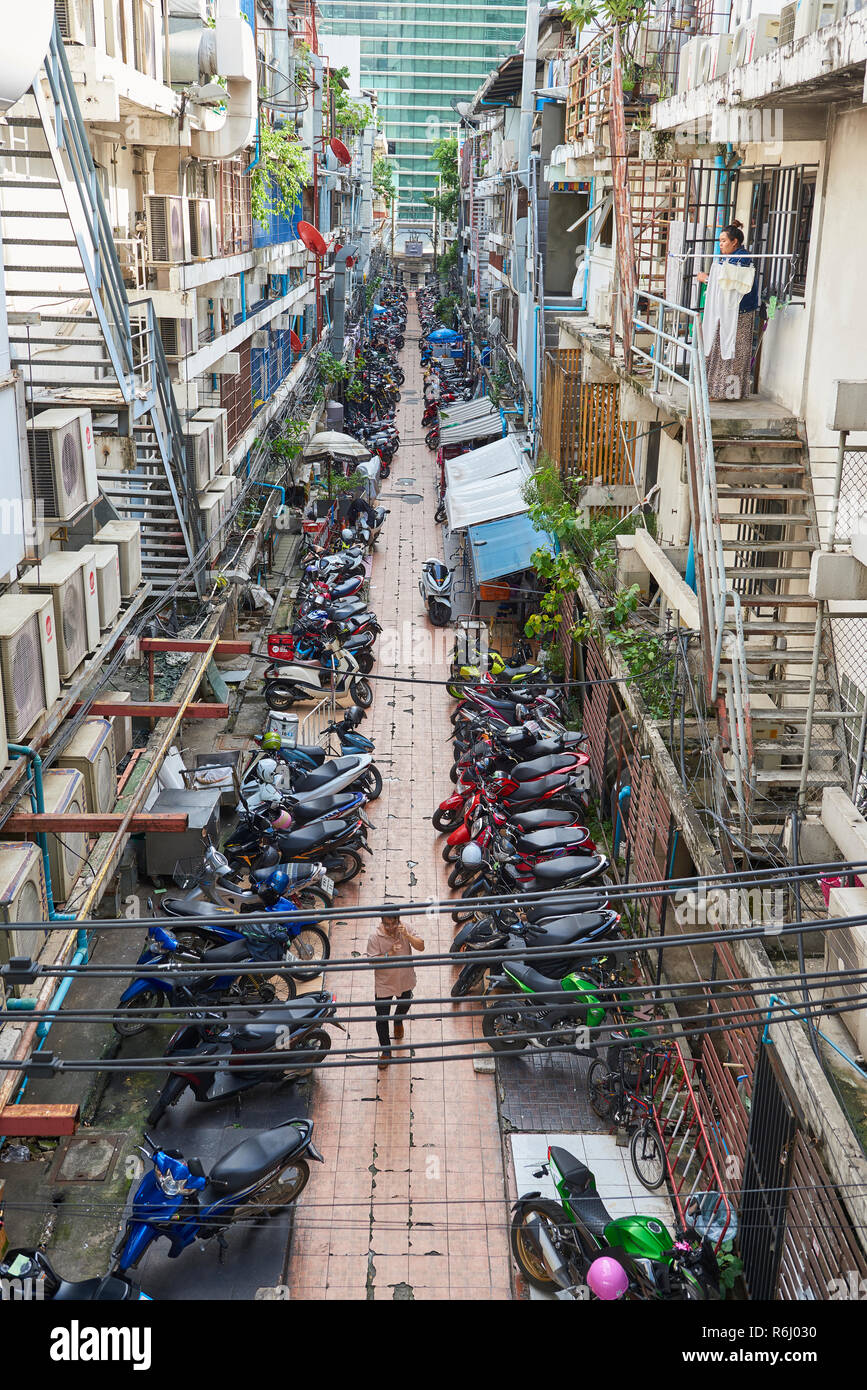 High angle shot of narrow street with several mopeds parked amongst residential buildings and pedestrian walking past. In Bangkok, Thailand. Stock Photo