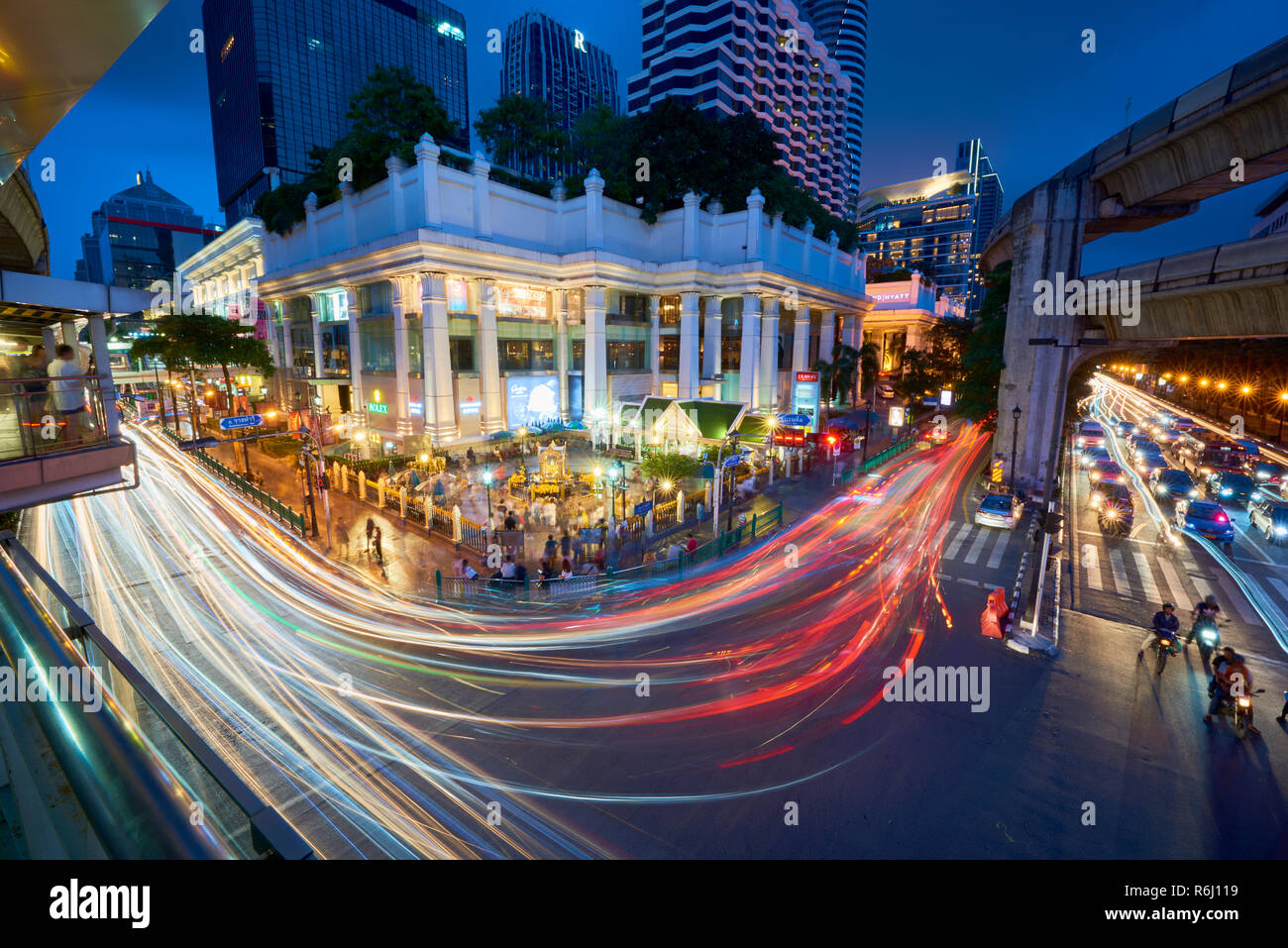 Creative high angle night shot of Ratchaprasong Intersection and Erawan Shrine in Bangkok, Thailand, with colourful light trail from cars driving past Stock Photo