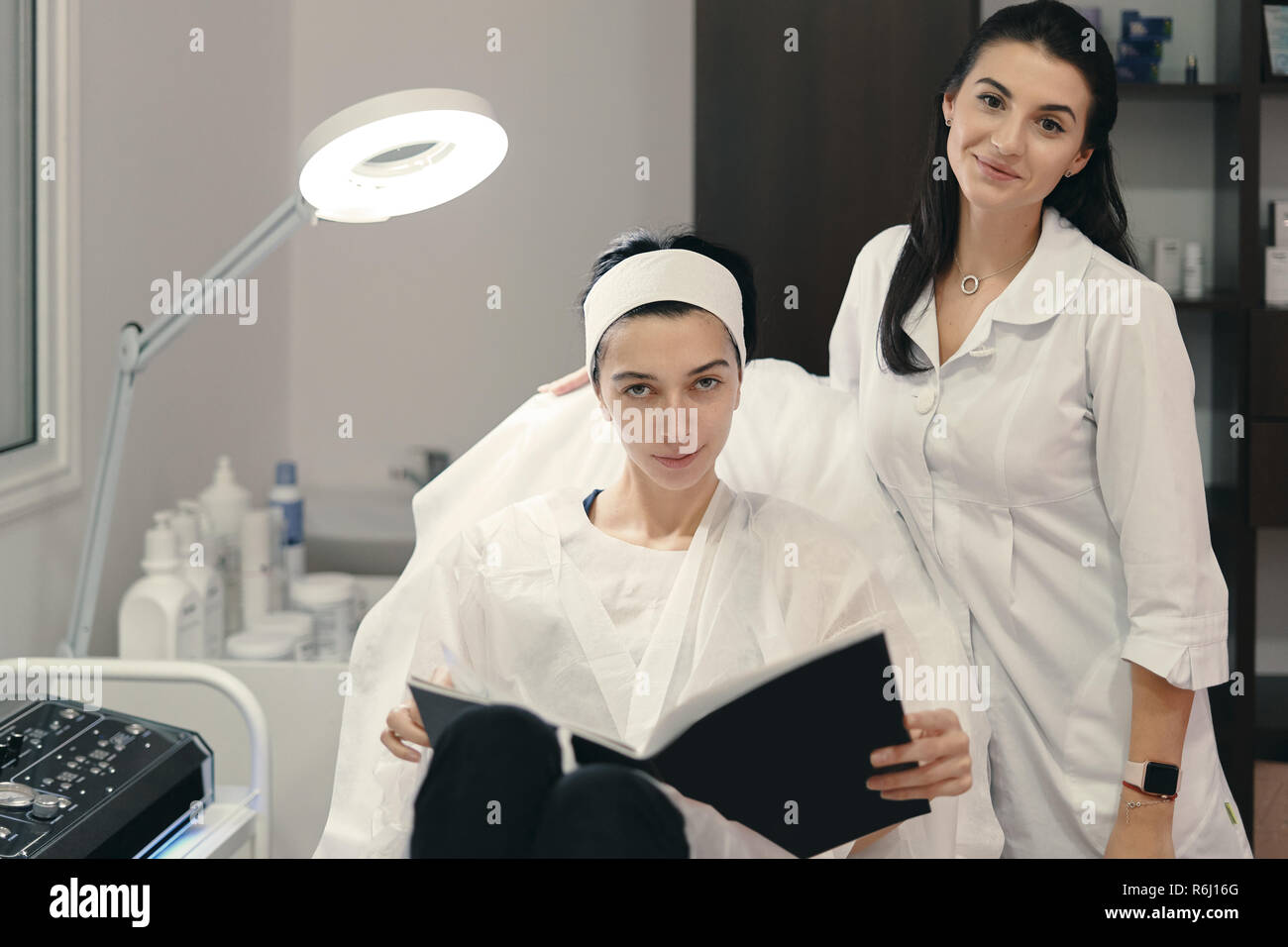 Pretty woman cosmetologist showing to her patient innovations in cosmetology in a magazine while getting ready for facial procedures. - Stock Image