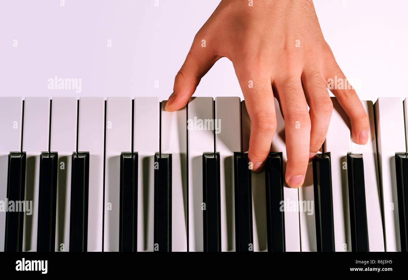 Pianist playing on a synthesizer, isolated on a gradient gray background - Stock Image
