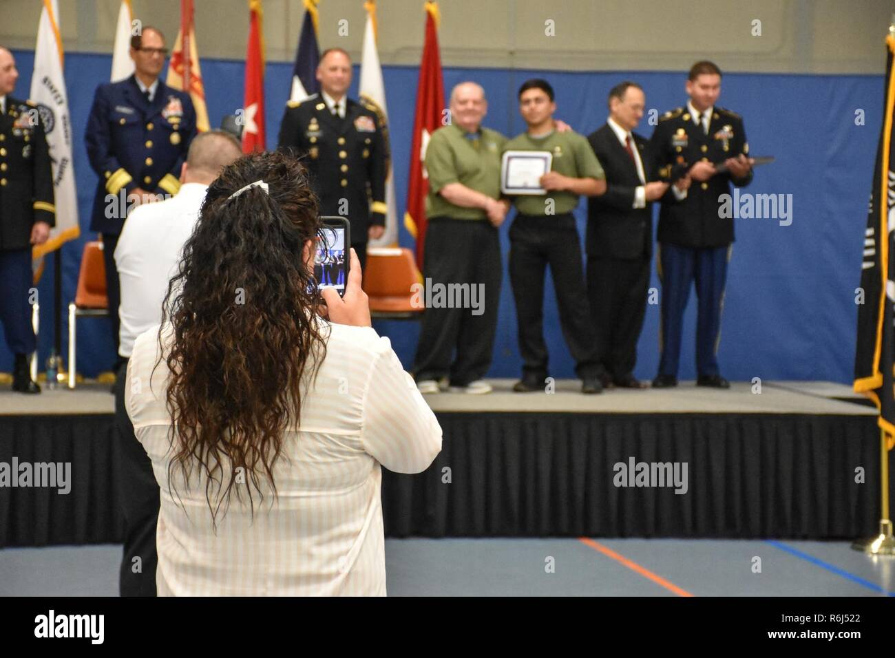 "A proud future U.S. Army Reserve mom takes photos as her son receives an ""Our Community Salutes"" certificate from Medal of Honor recipient Command Sergeant Major (Ret.) Kenneth E. Stumpf and Fort McCoy Senior Commander and 88th Regional Support Command Commanding General, Maj. Gen. Patrick Reinert during an ""Our Community Salutes"" event at Fort McCoy, Wisconsin on Armed Forces Day, May 20, to recognize and honor graduating high school seniors who have committed to enlist in the Armed Forces following high school graduation. Stock Photo"