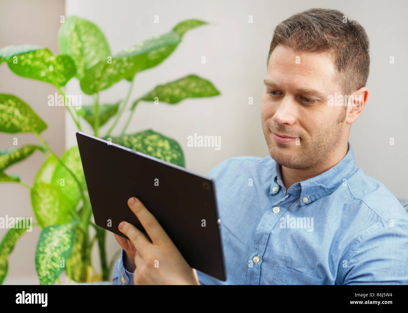Handsome unshaved man making shopping online. - Stock Image