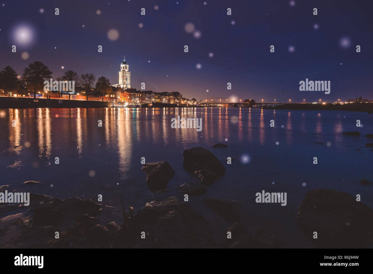 Deventer at night with view over the river Ijssel from a beach. The tower church is towered above the beautifully-featured cityscape. Stock Photo