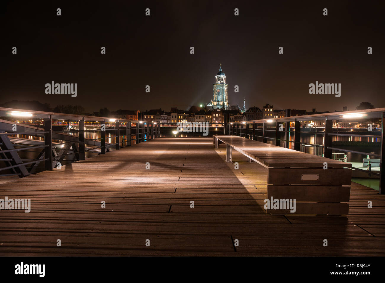 Deventer at night with view from a jetty over the river Ijssel. The tower of the Lebuinus church is towered above the beautifully lit cityscape. Stock Photo