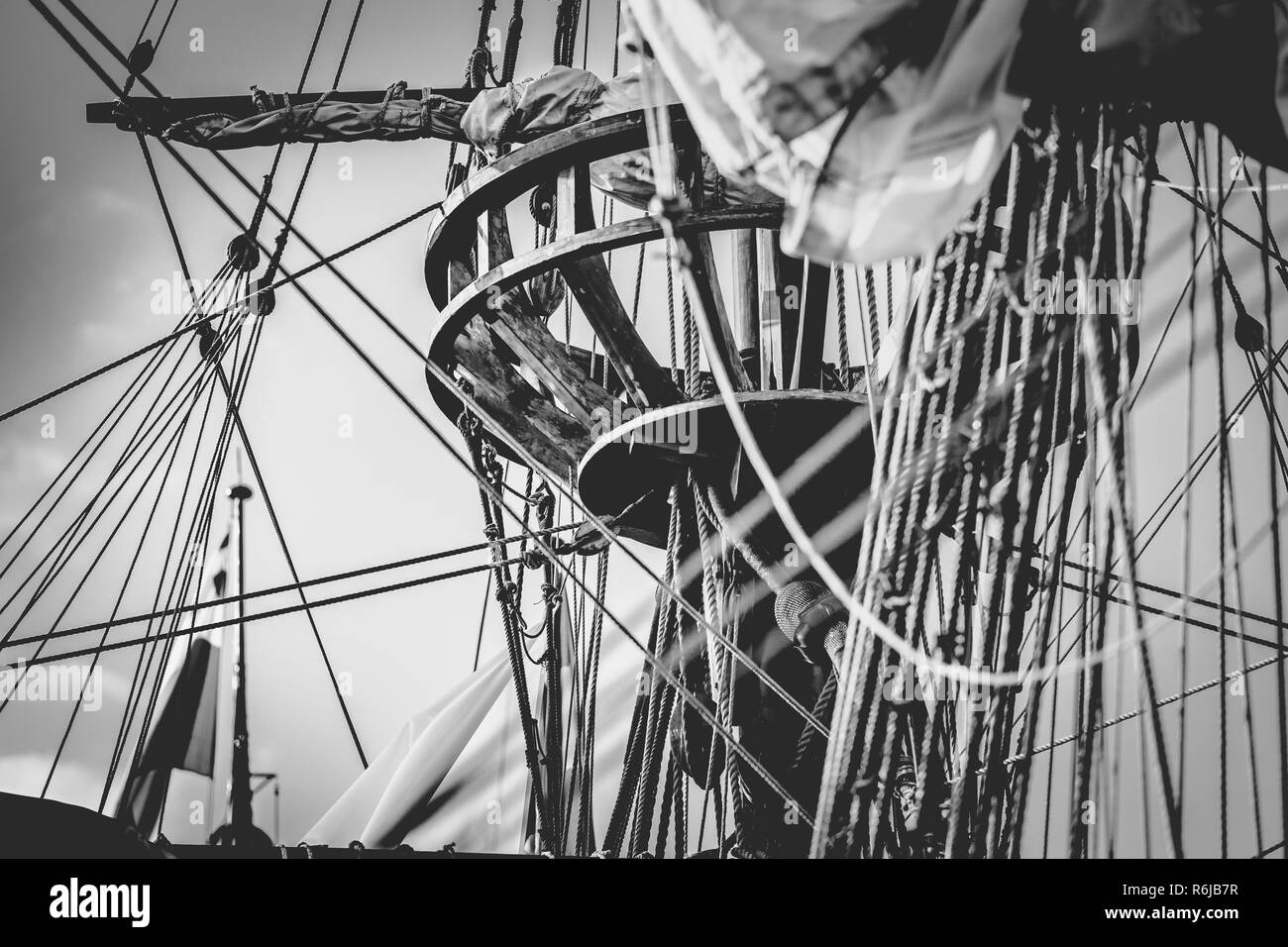 Detail of mast of ship. Detailed rigging with sails. Vintage sailing ship block and tackle. handmade woodwork statues and a forest on boat masts - Stock Image