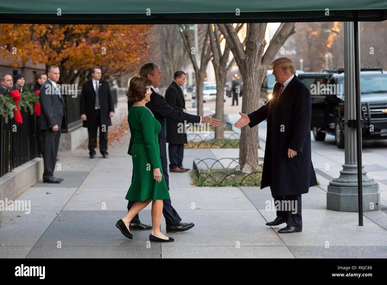 Washington DC, USA. 4th December, 2018. U.S President Donald Trump reaches out to greet former President George W. Bush and former First Lady Laura Bush outside Blair House December 4, 2018 in Washington, DC. Bush is stay at Blair House to attend the memorial service for his father the late President George H.W. Bush. Credit: Planetpix/Alamy Live News - Stock Image