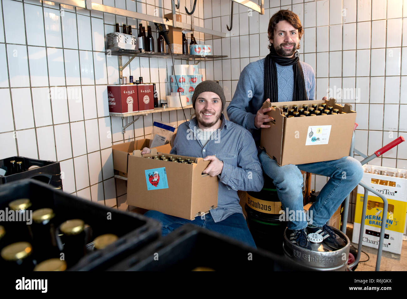 """Kassel, Germany. 22nd Nov, 2018. Erik Schäfer (l) and Johannes Alt, owners of the brewery Steckenpferd, each sit with a box of Craft Beer in the lager of the brewery. (to dpa """"Successful in the niche - Craft beer brewers assert themselves on the market"""" of 06.12.2018) Credit: Swen Pförtner/dpa/Alamy Live News Stock Photo"""