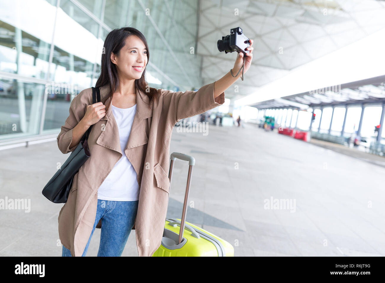 Woman using digital camera taking selfie in airport - Stock Image
