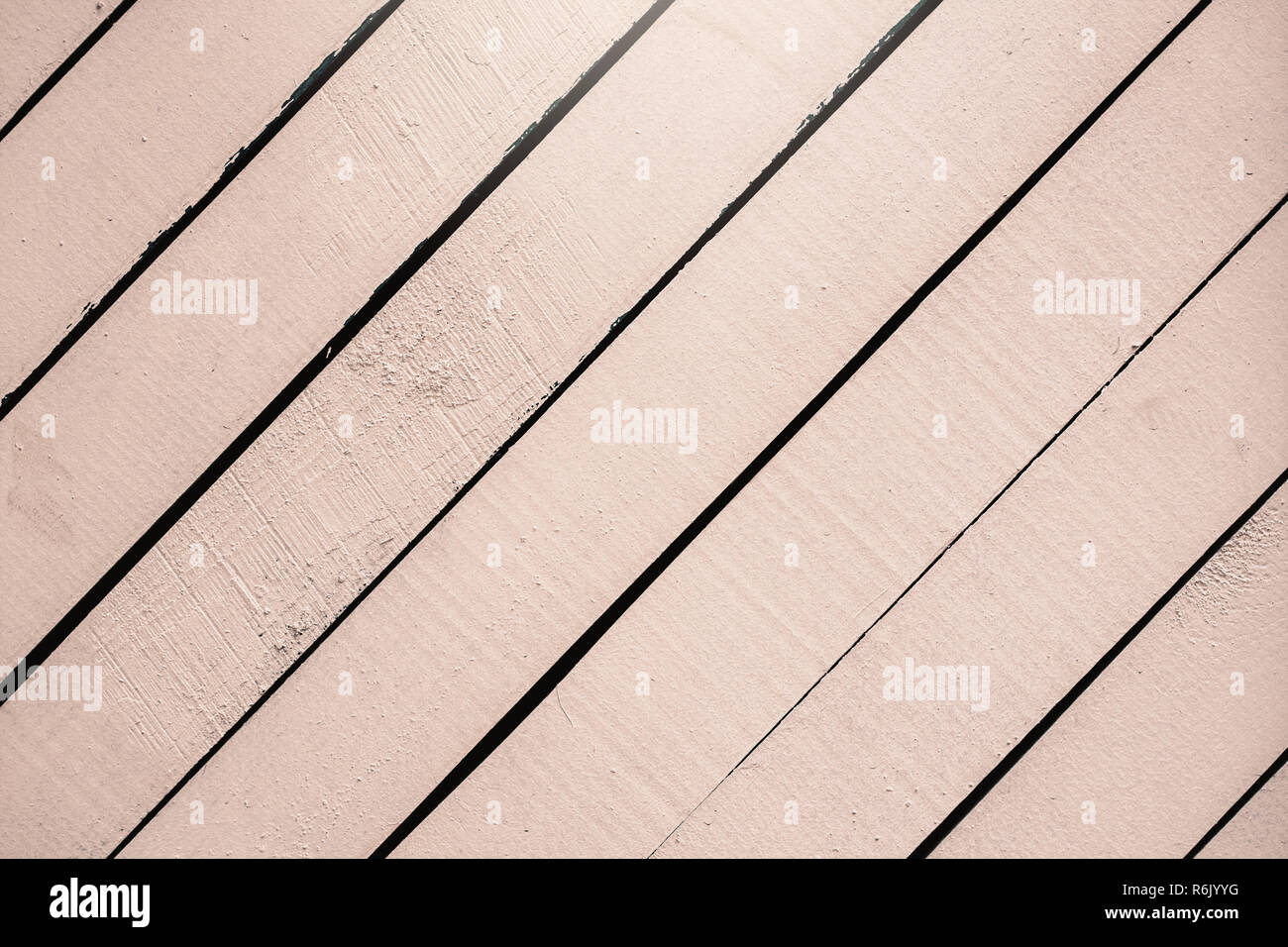 Light pink wooden surface, texture close-up. Rustic natural diagonal planks with cracks, scratches for modern design, patterns, background, copy space - Stock Image