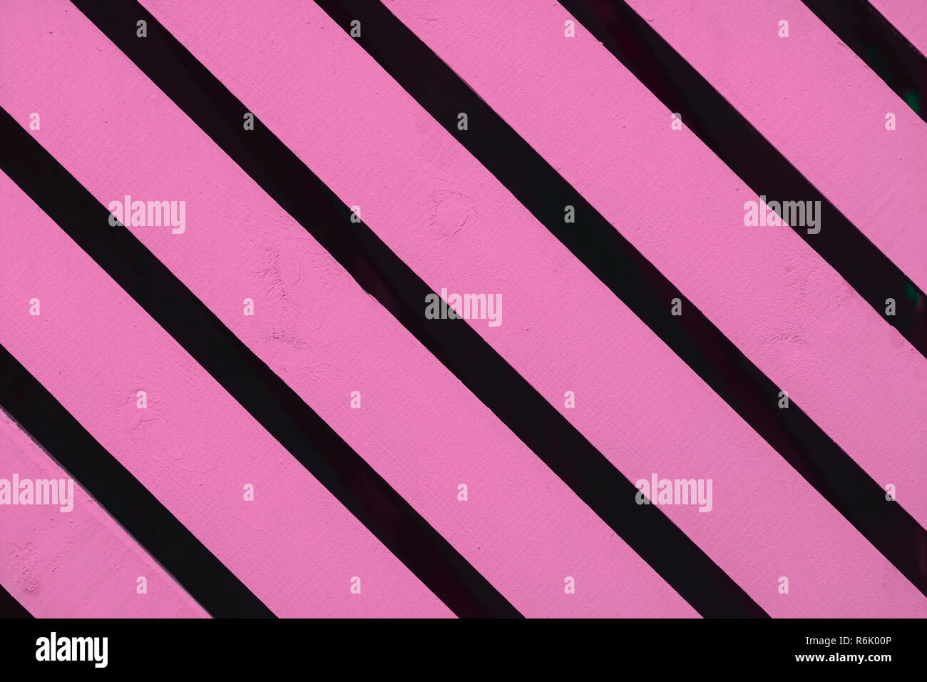 Bright pink wooden surface, texture close-up. Rustic natural diagonal planks with cracks, scratches, textured background, copy space - Stock Image