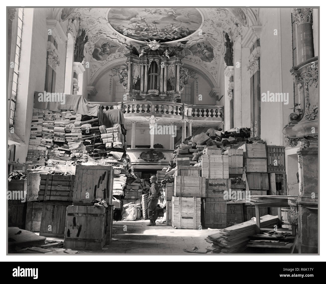 "Vintage Nazi Loot Plunder WW2 World War II American military   ""Monument Men "" encountered German Nazi loot repositories such as this one all across Europe. Here, piles of boxes, records, and clothing are guarded by an American GI inside a church in Ellingen, Germany. The church had been used by the Nazis as a secret depot for clothing 'requisitioned' from Belgium France and Holland 1945 Stock Photo"