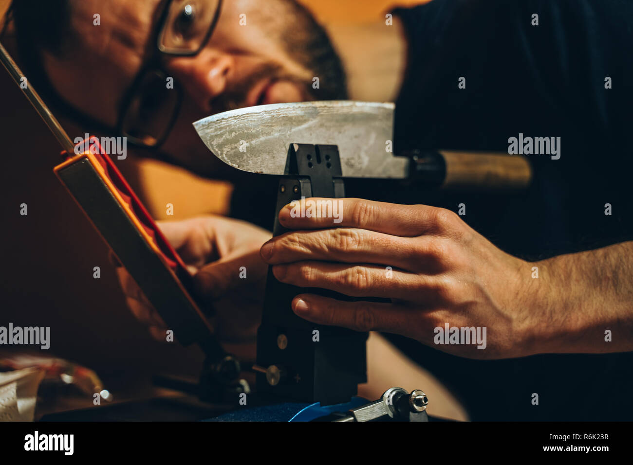 caucasian man sharpening a japanese kitchen knife with a modern whetstone device - Stock Image