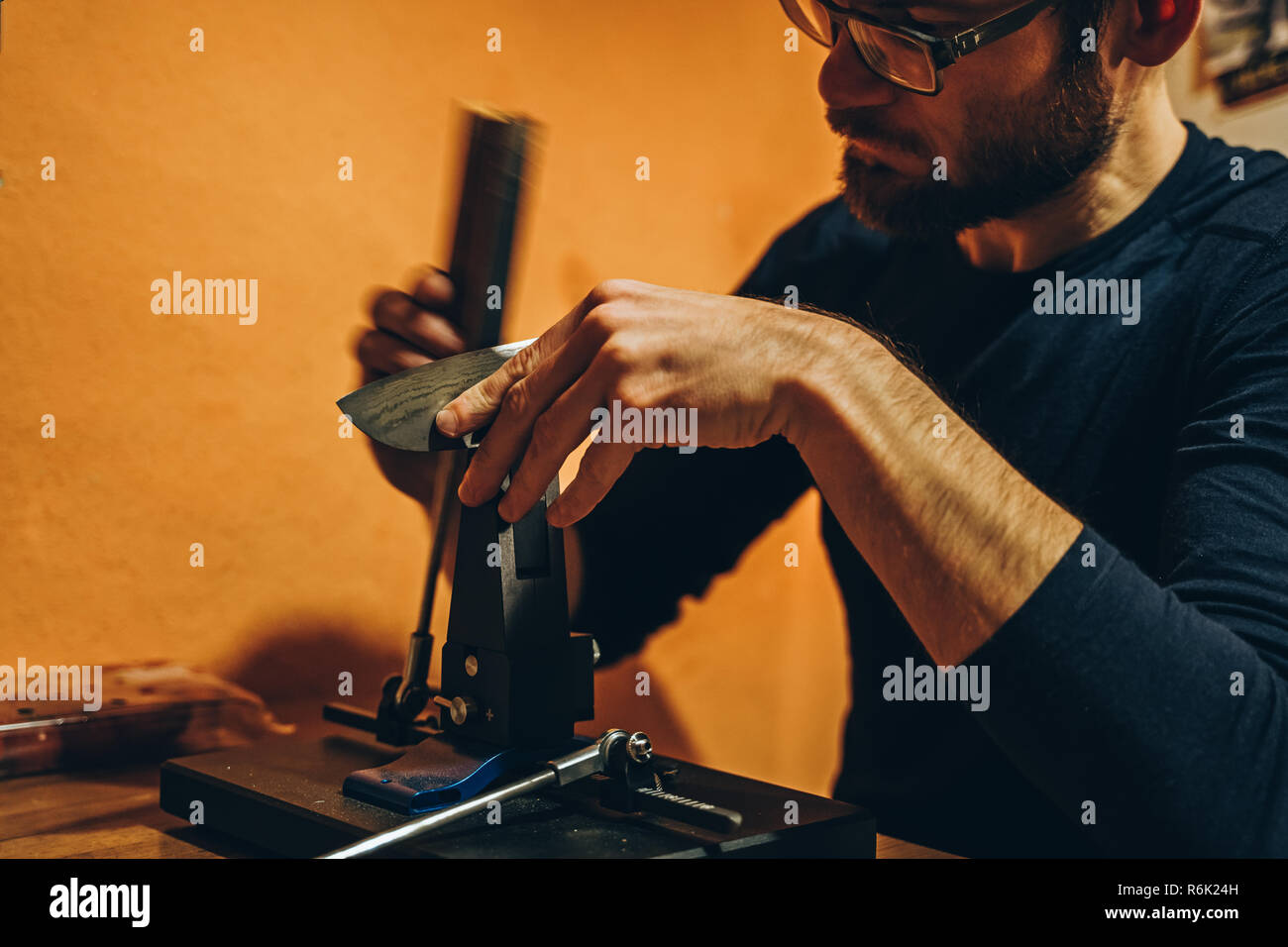 photo of caucasian man sharpening a japanese kitchen knife with a modern whetstone device - Stock Image