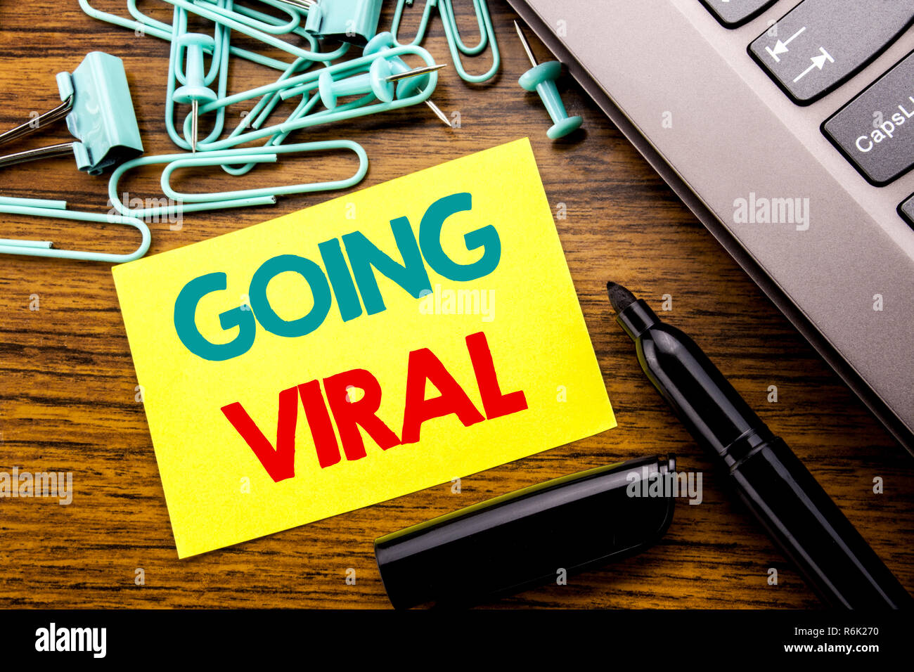 Handwriting Announcement text showing Going Viral. Business concept for Social Viral Business written on sticky note paper on the wooden background next to the laptop keyboard With marker Stock Photo
