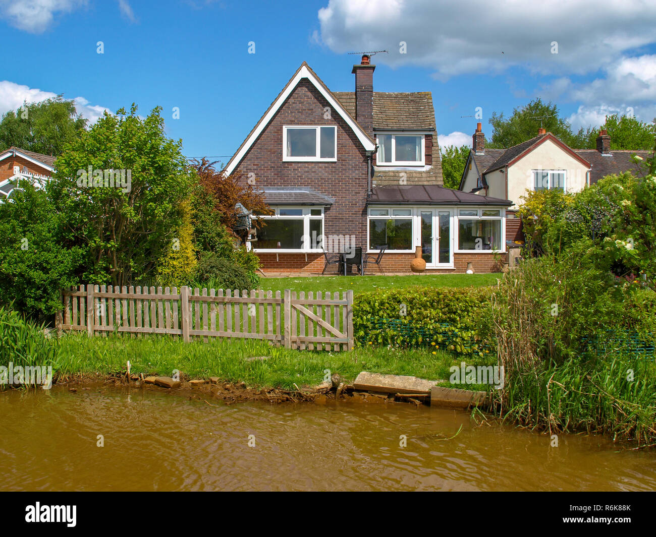 Canalside house on the Trent and Mersey Canal in the West Midlands in England. View from the boat. - Stock Image