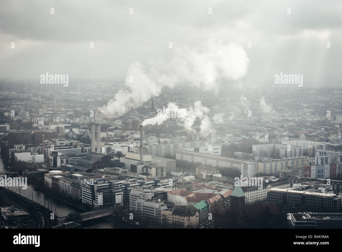 Factory in the center of Berlin city with smoke going from chimneys. Aerial view of industrial city - Stock Image