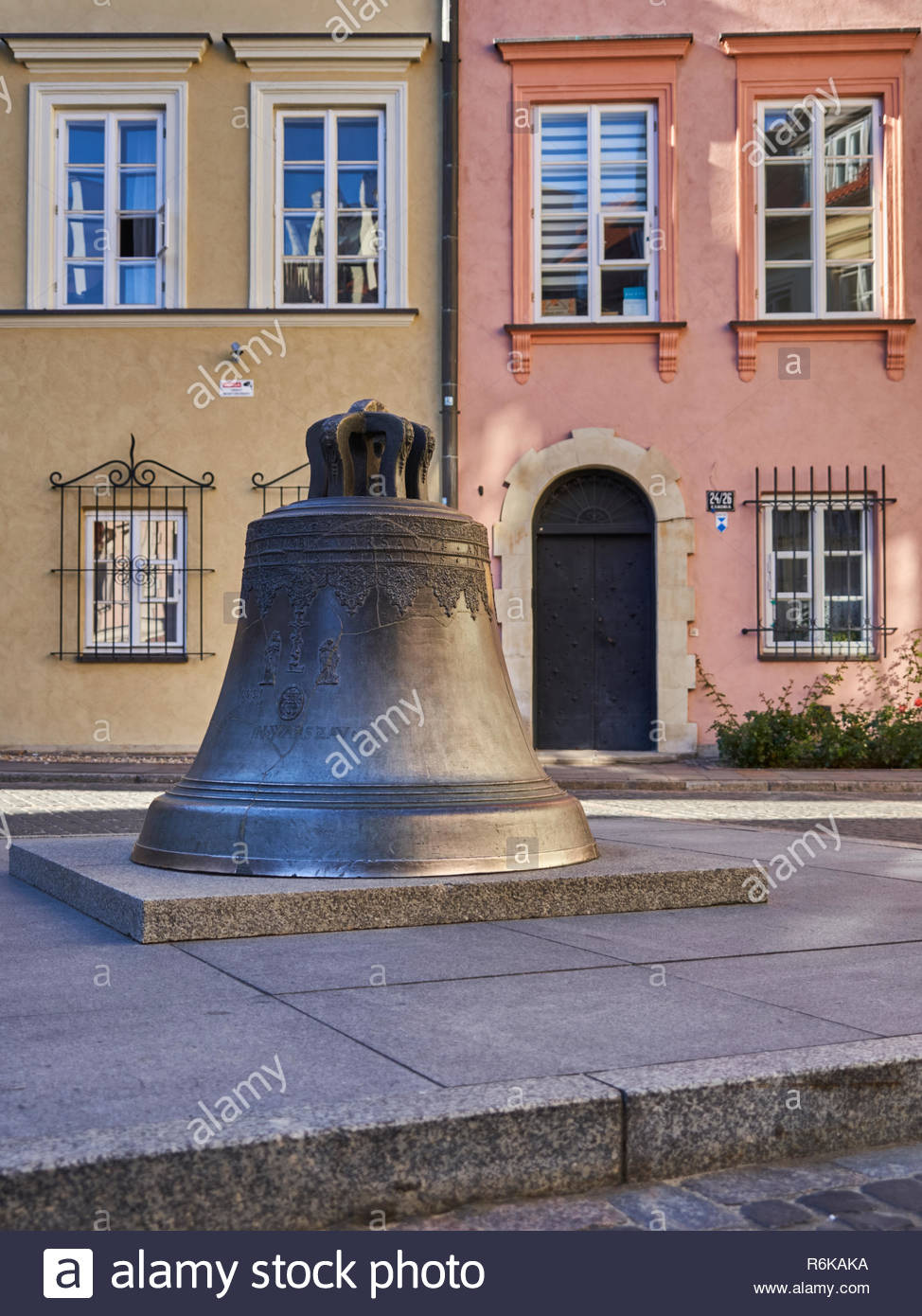 The Wishing Bell (Dzwon na Kanonii) in Warsaw, Poland, with a couple of colourful buildings in the background. - Stock Image