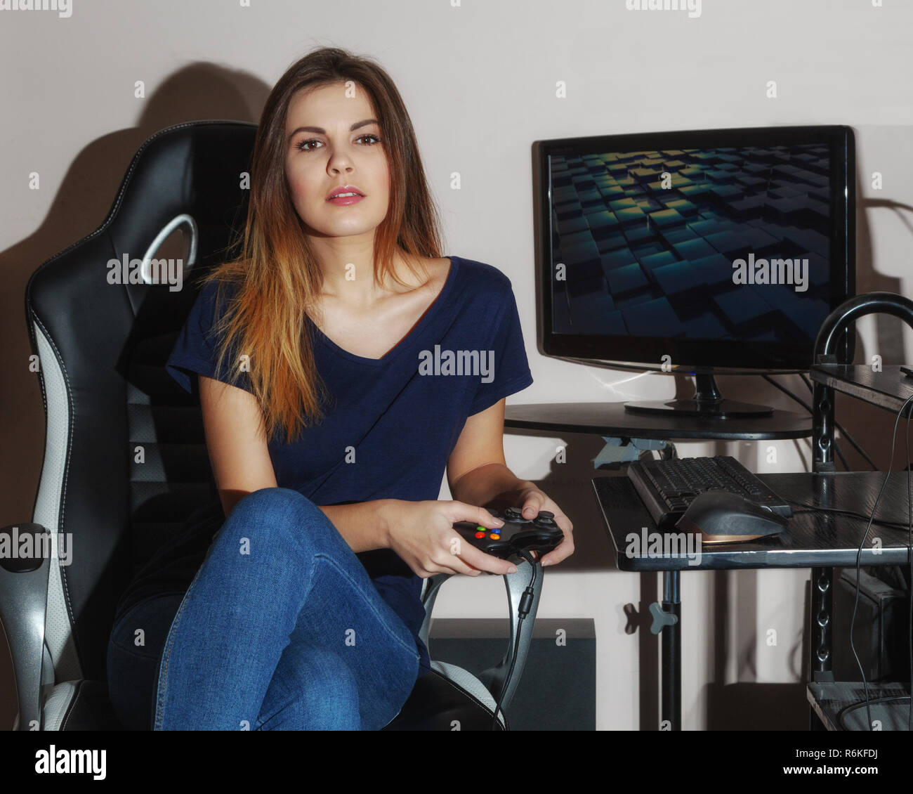A young woman with a game controller in hand - Stock Image