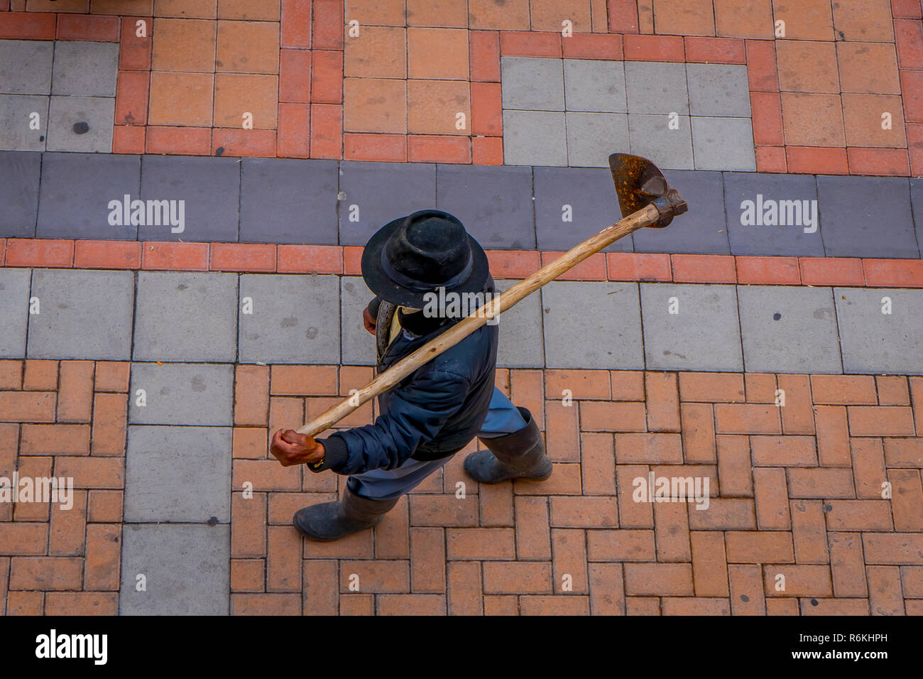 Above view of unidentified indigenous man walking in the sidewalk and holding in his back a farm machine, located in the city of Cotacachi in Ecuador. Stock Photo
