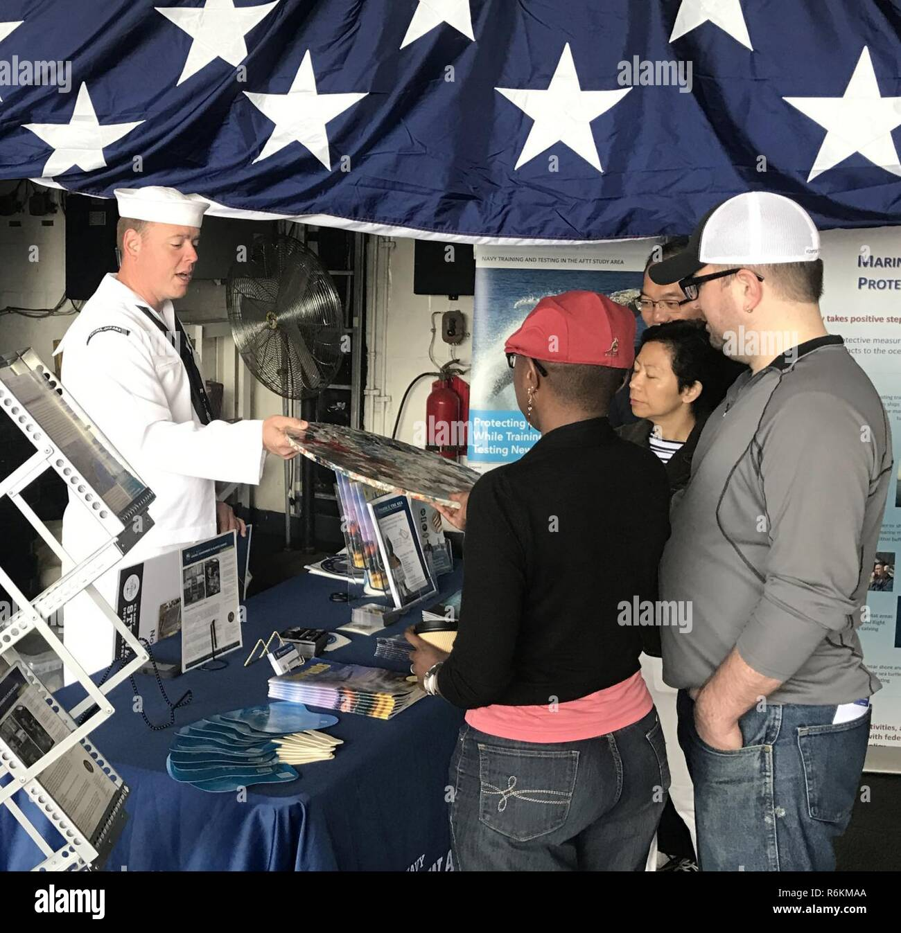 """NEW YORK (May 28, 2017) Mass Communication Specialist 1st Class J.R. Peregrino, assigned to U.S. Fleet Forces Command, discusses plastic waste processing with visitors at the """"Stewards of the Sea: Defending Freedom, Protecting the Environment"""" exhibit aboard the guided-missile cruiser USS Monterey (CG 61) at the Brooklyn Cruise Terminals during Fleet Week New York. The Navy employs every means available to mitigate the potential environmental effects of our activities without jeopardizing the safety of our Sailors or impacting our Navy readiness mission. Stock Photo"""