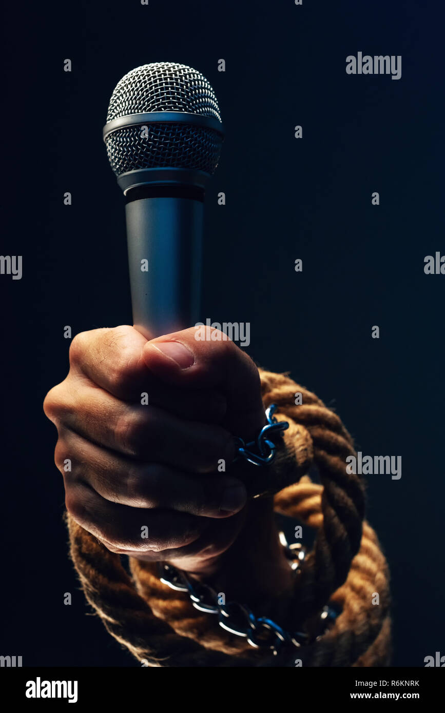Freedom of the press and journalism, conceptual image with microphone in male hand tied with chains and ropes, low key image - Stock Image