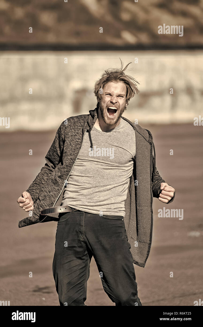Man with angry face shouting in sporty clothes outdoors, vintage filter. Anger, aggression, emotions concept. - Stock Image