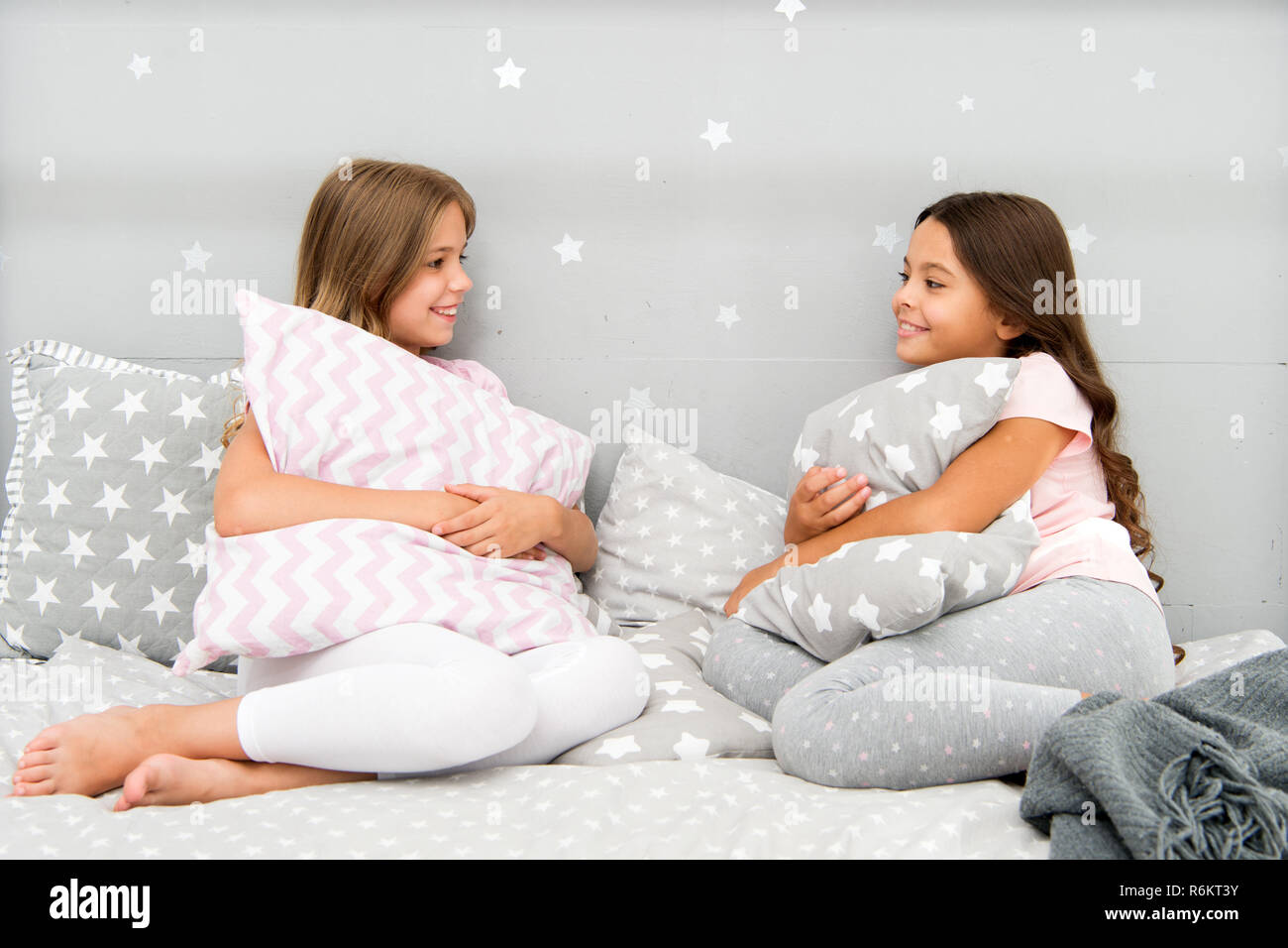 Sisters communication. Sisters communicate while relax in bedroom. Family time. Children relax and having fun in evening. Sisters leisure. Girls in cute pajamas spend time together in bedroom. - Stock Image