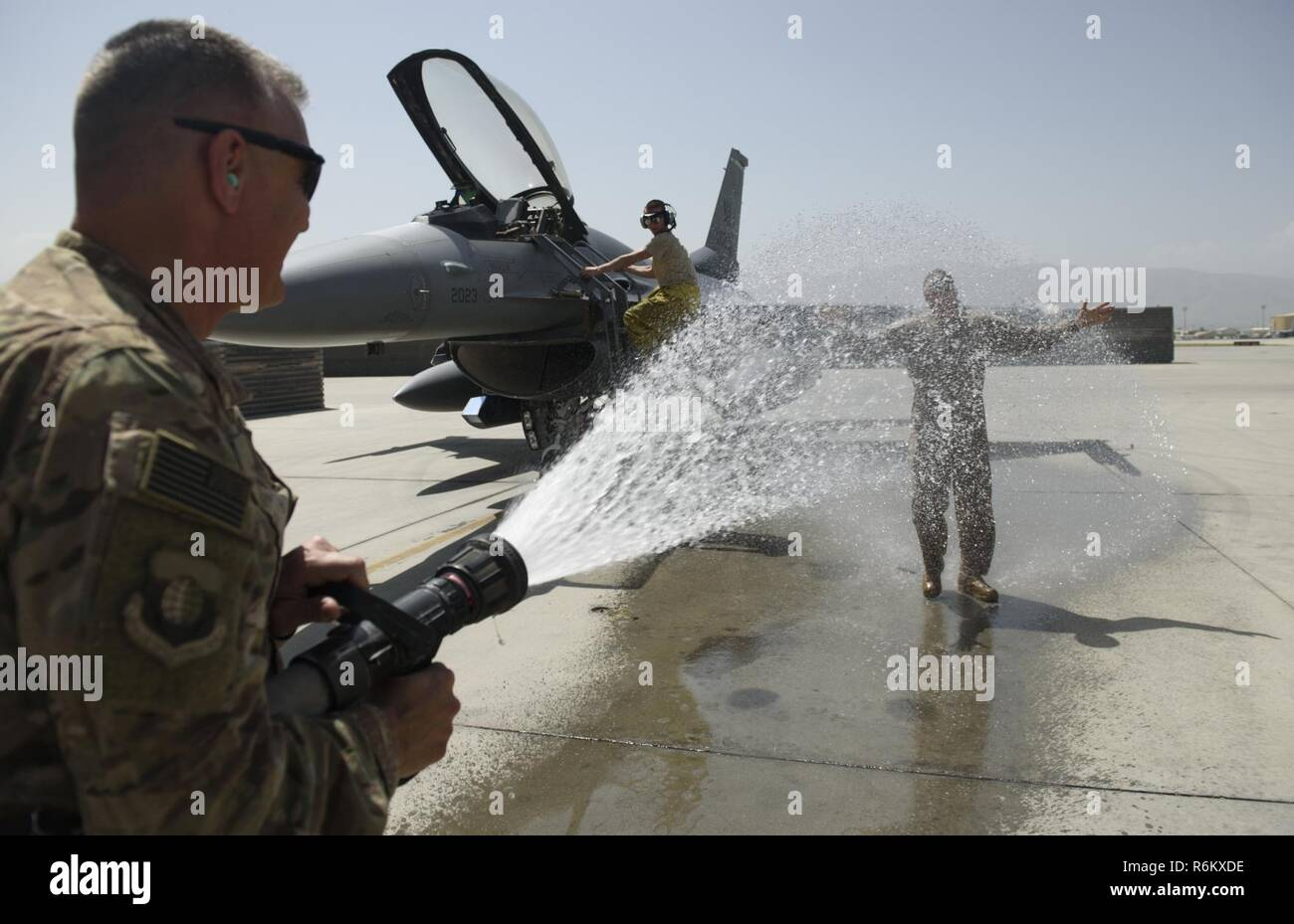Chief Master Sgt. Peter Speen, command chief of the 455th Air Expeditionary Wing, hoses down Brig. Gen. Jim Sears at Bagram Airfield, Afghanistan, May 22, 2017. Sears, commander of the 455th AEW, conducted his fini flight out of Bagram Airfield. The fini flight is a time-honored military aviation tradition marking the last flight of a commander's tour. Stock Photo