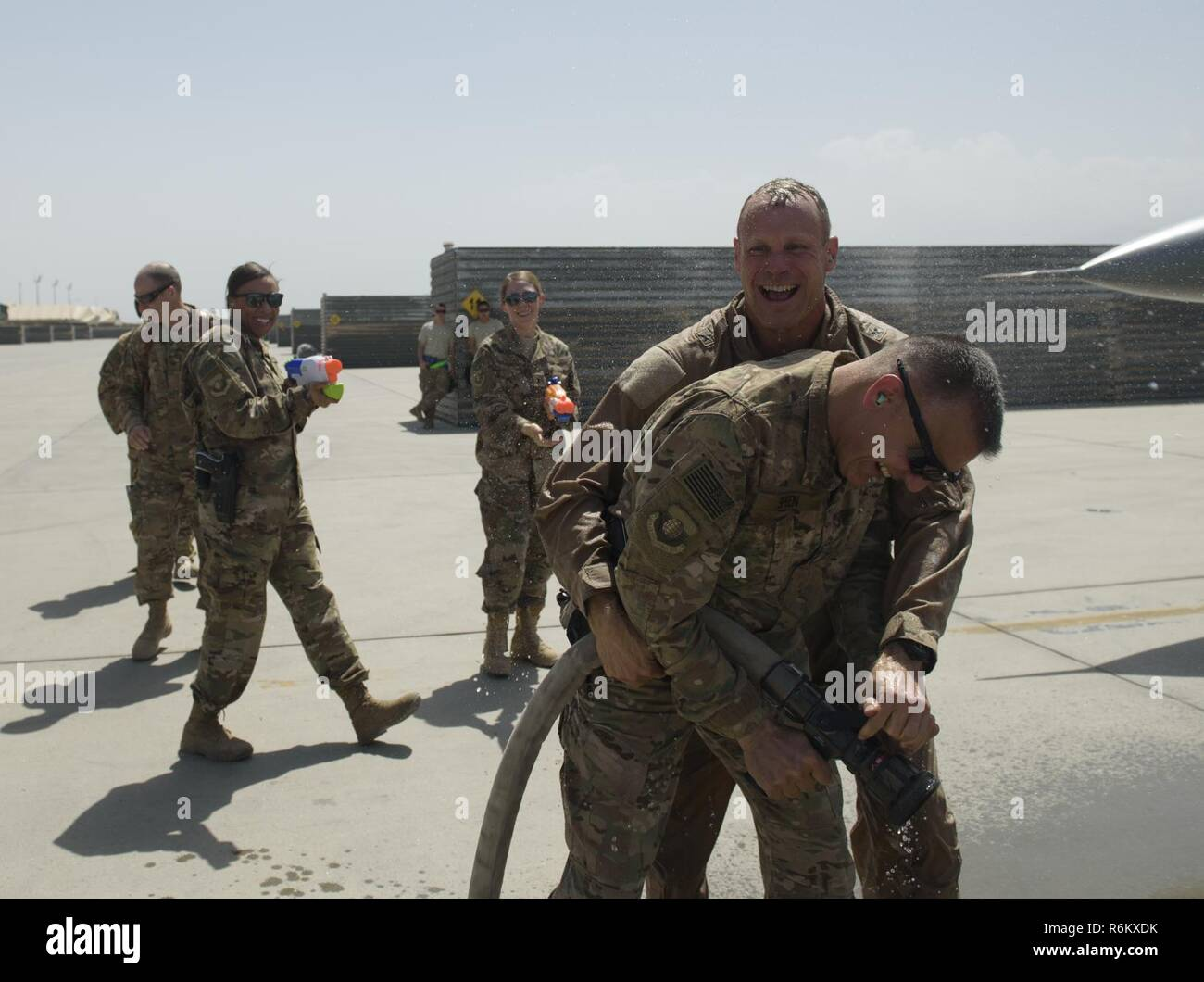 Brig. Gen. Jim Sears, commander of the 455th Air Expeditionary Wing, wrestles a fire hose away from Chief Master Sgt. Peter Speen, command chief of the 455th AEW, after completing his fini flight at Bagram Airfield, Afghanistan, May 22, 2017. Sears, who commanded the 455th AEW for the last 12 months, is a command pilot with more than 3,200 flying hours, including combat missions over Iraq and Afghanistan. Stock Photo