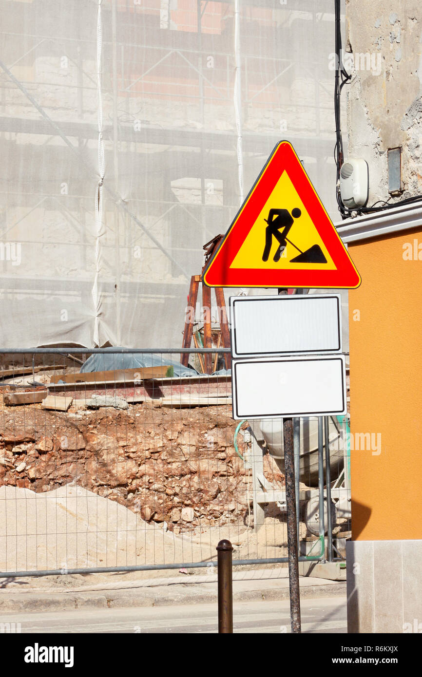 Road construction work and sign at a construction site. Warning sign under construction. Road works traffic sign in a building site - beware. - Stock Image