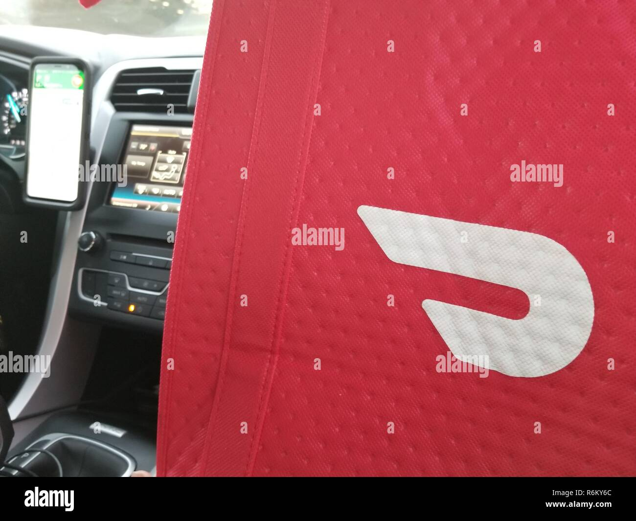 Insulated delivery bag with logo for food delivery gig economy app Doordash, in the front seat of a Doordash delivery vehicle in Walnut Creek, California, with smartphone and navigation app visible in background, October 9, 2018. () Stock Photo