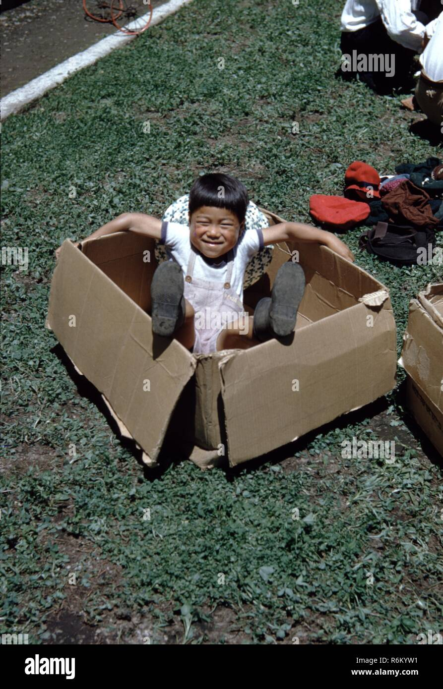 Historical photograph of a young Japanese boy playing in a cardboard box in a field in Japan, 1955. - Stock Image