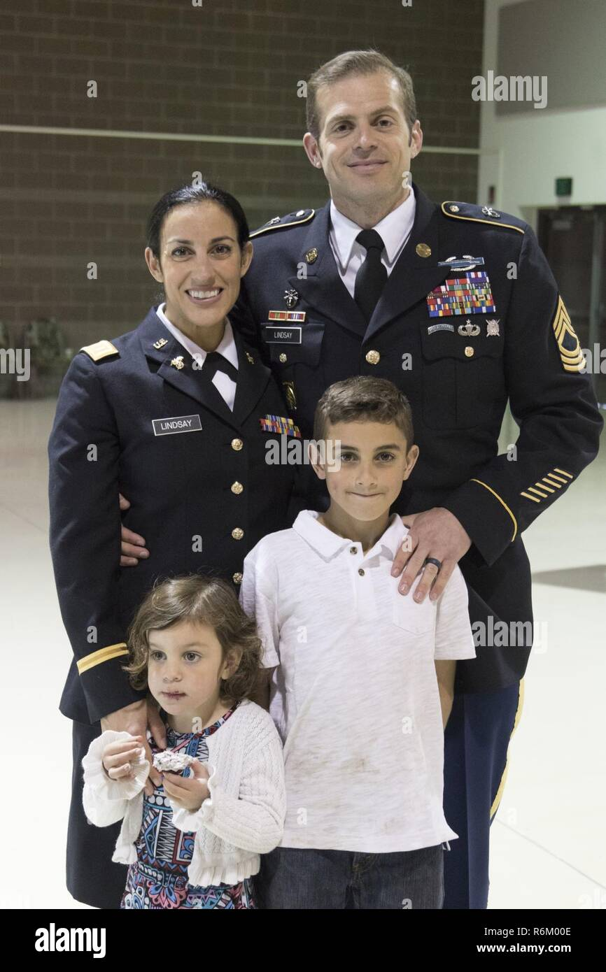 2nd Lt. Marisa Lindsay poses with her husband, Master Sgt. Michael Lindsay, Special Forces Advisor with the 1-196th Infantry Regiment, son Liam, 10, and daughter Esmarin, 4, after a commissioning ceremony at the National Guard armory on Joint Base Elmendorf-Richardson, Alaska, May 21, 2017. Lindsay earned the distinction of Honor Graduate and was recognized with the High Physical Fitness Award from the Officer Candidate School at the Alabama Military Academy. - Stock Image