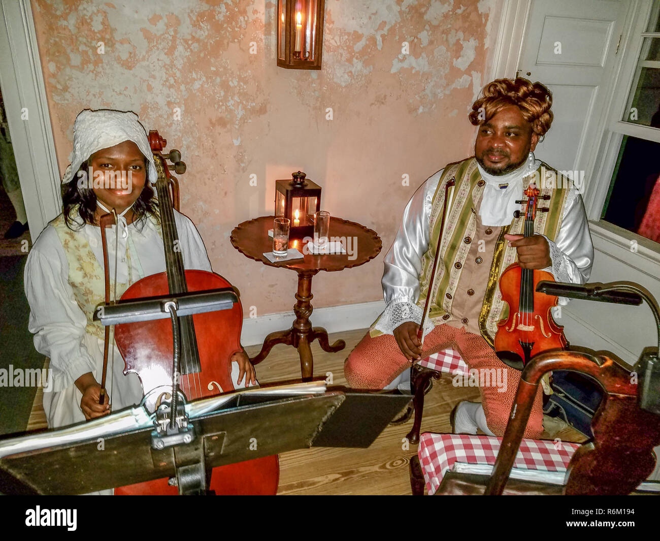 Woman and man playing the part of house slaves during recreation of a dinner with 'George Washington,' attended by island visitors for 'Dinner With George.' - Stock Image
