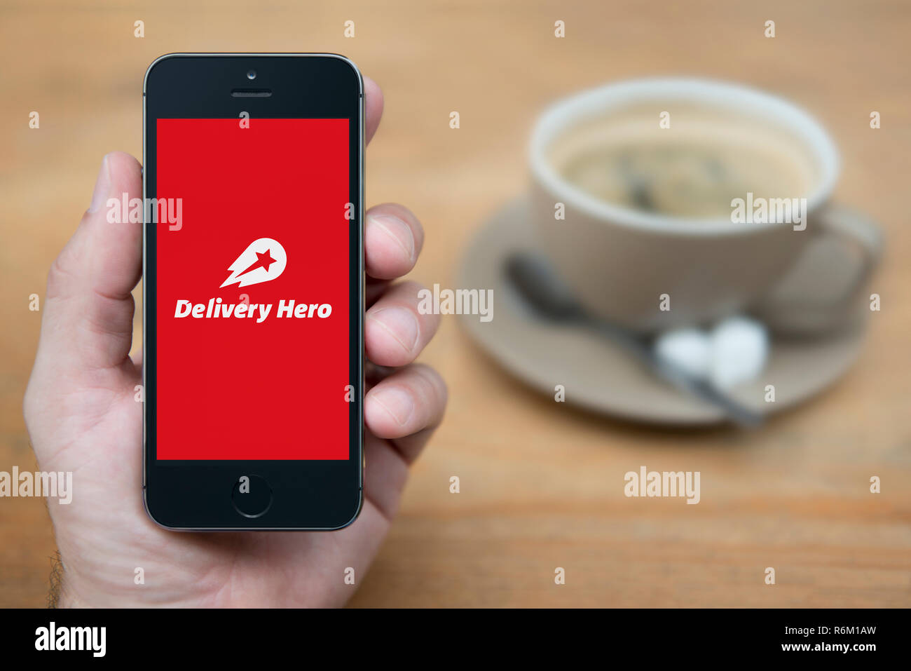 A man looks at his iPhone which displays the Delivery Hero logo (Editorial use only). - Stock Image