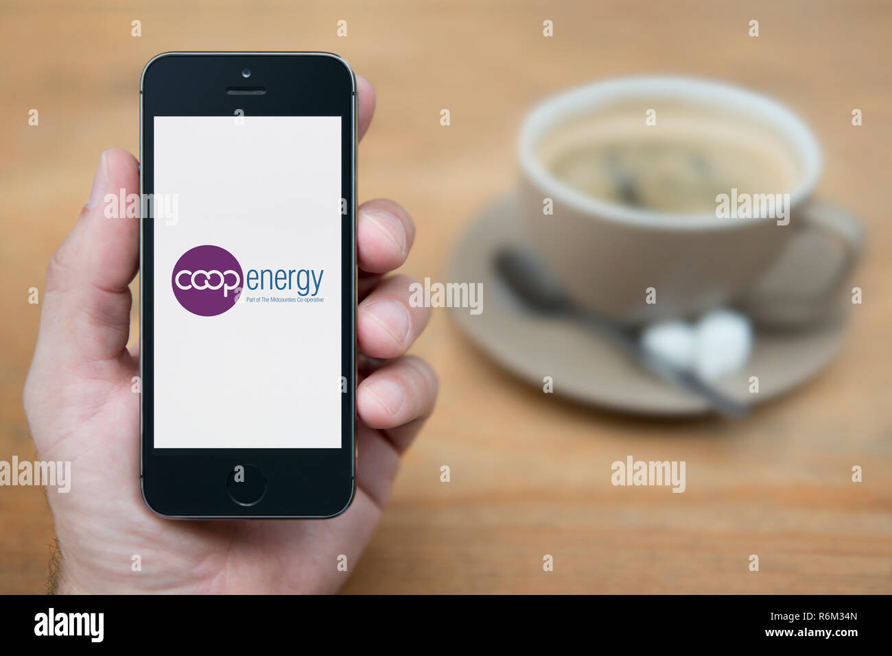 A man looks at his iPhone which displays the Co-op Energy logo (Editorial use only). - Stock Image