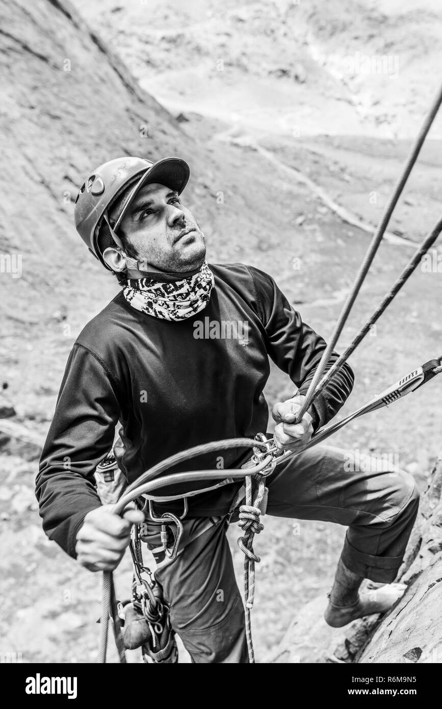 Face expressions while a climber climb a big wall inside the Andes, an amazing adventure. Smile on his faces while going to the mountain summit - Stock Image