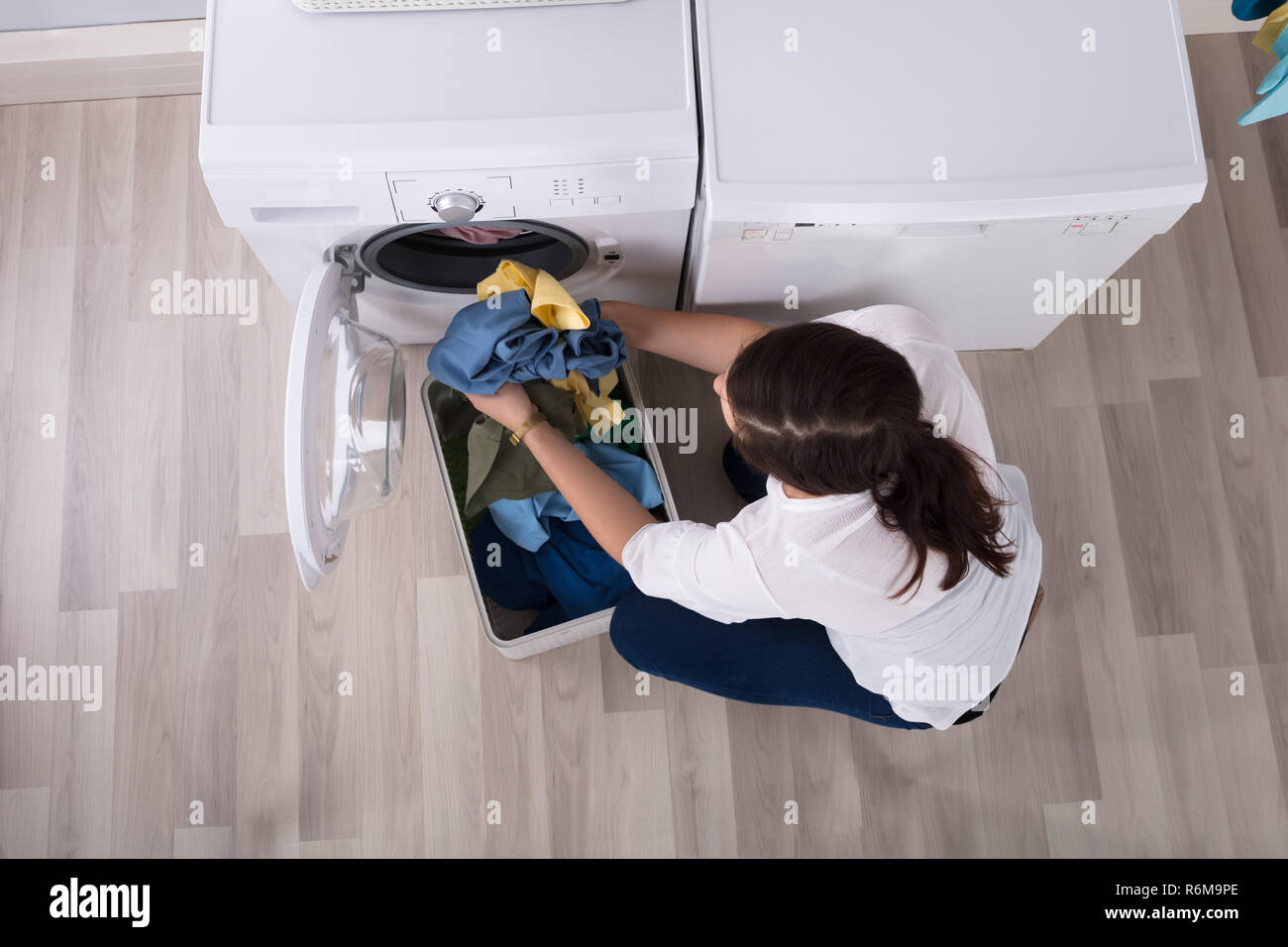 Elevated View Of A Woman Loading Clothes In Washing Machine Stock Photo
