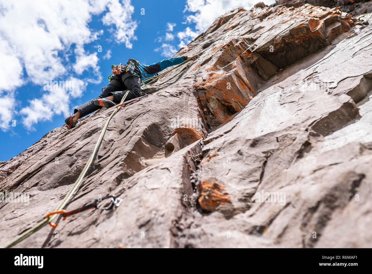 The last movements to reach the summit by a male climber. Rock climbing inside Andes mountains and valleys at Cajon del Maipo, an amazing place Stock Photo