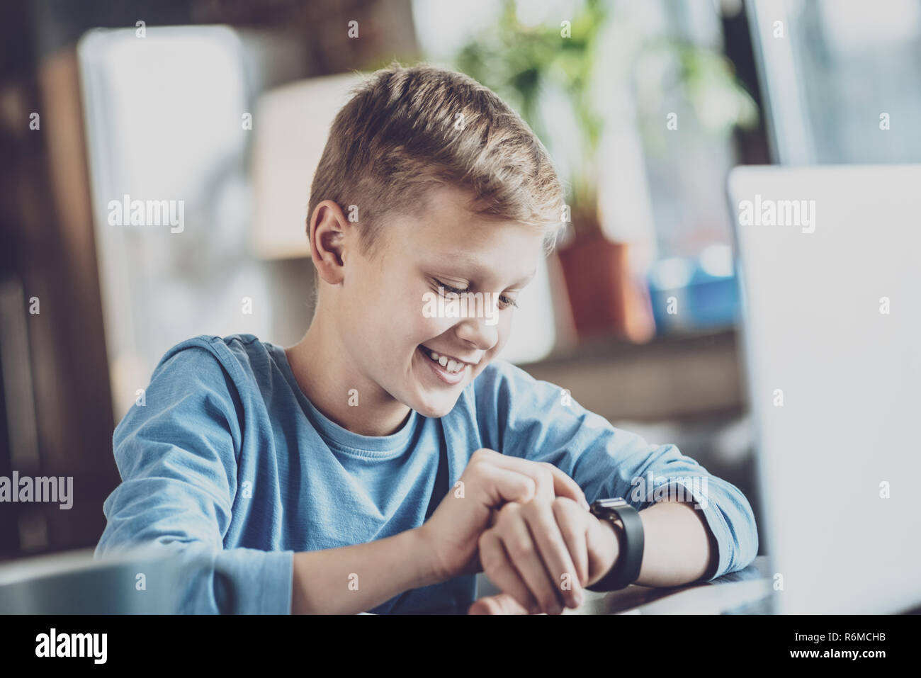 Portrait of delighted pupil that checking time - Stock Image