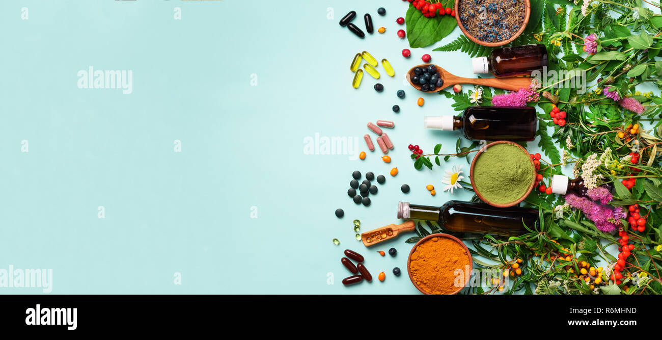 Holistic medicine approach. Healthy food eating, dietary supplements, healing herbs and flowers. Turmeric, dried lavender, spirulina powder in wooden  - Stock Image