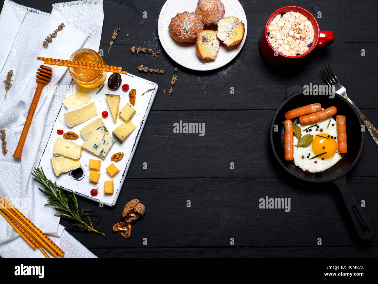 fried eggs with sausages in a frying pan and types of cheese Stock Photo