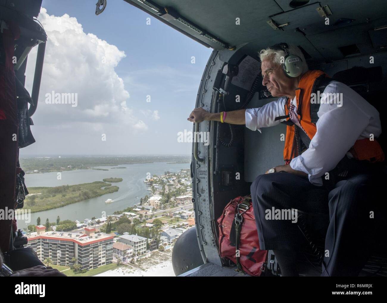 Congressman Charlie Crist, U.S. Representative for Florida's 13th District, keeps a eye on the coastline during an aerial assessment of beach erosion along Pinellas County, Florida's coast, Tuesday, May 30, 2017. Coast Guard Air Station Clearwater MH-60 Jayhawk helicopter crew members provided the overflight for the congressman and Army Corps of Engineers personnel. U.S. Coast Guard by Petty Officer 1st Class Michael De Nyse - Stock Image