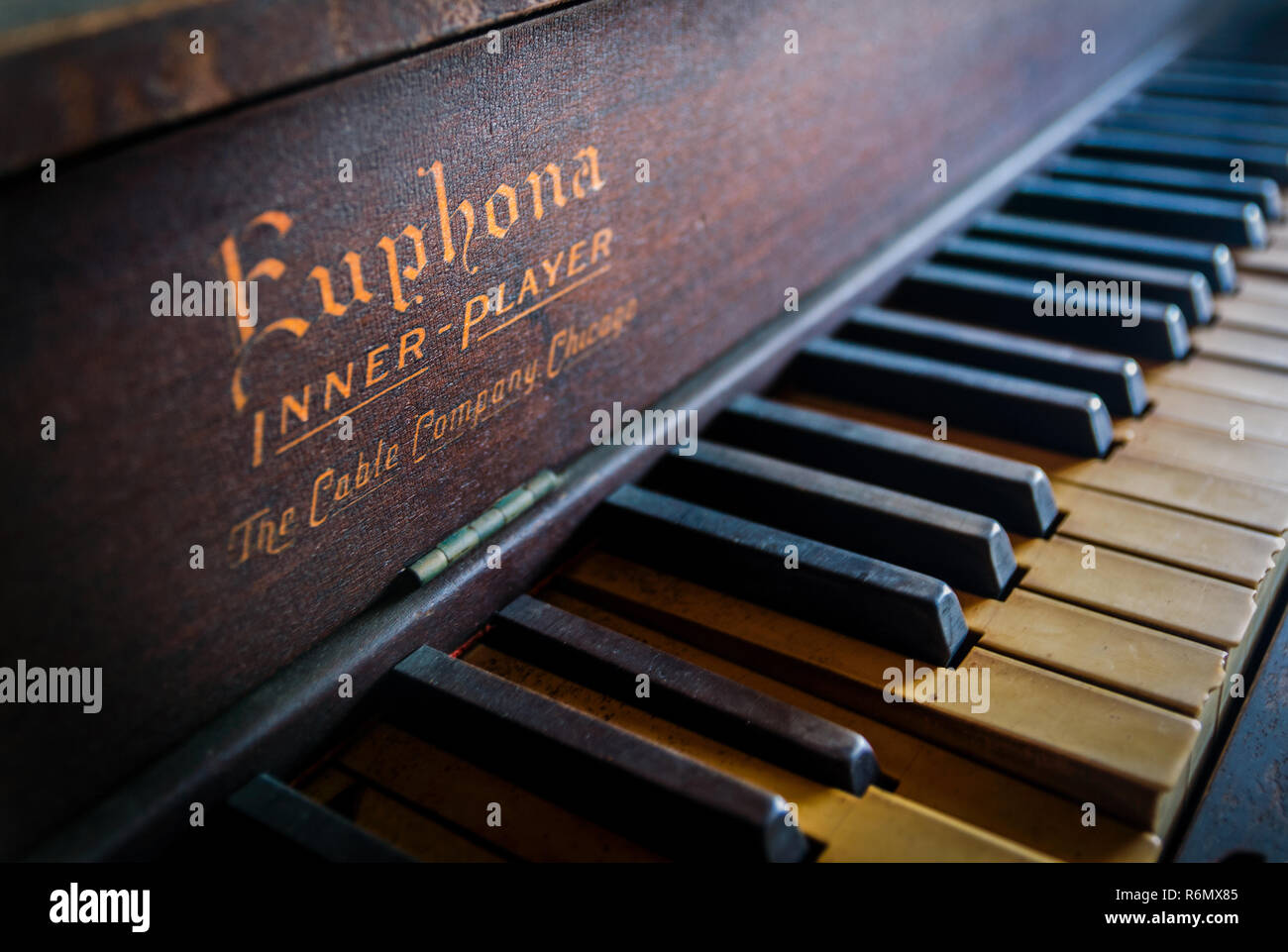 Morning sunlight streams across the keys of an antique Euphona Inner-Player piano for sale at a thrift store in Reform, Alabama. - Stock Image