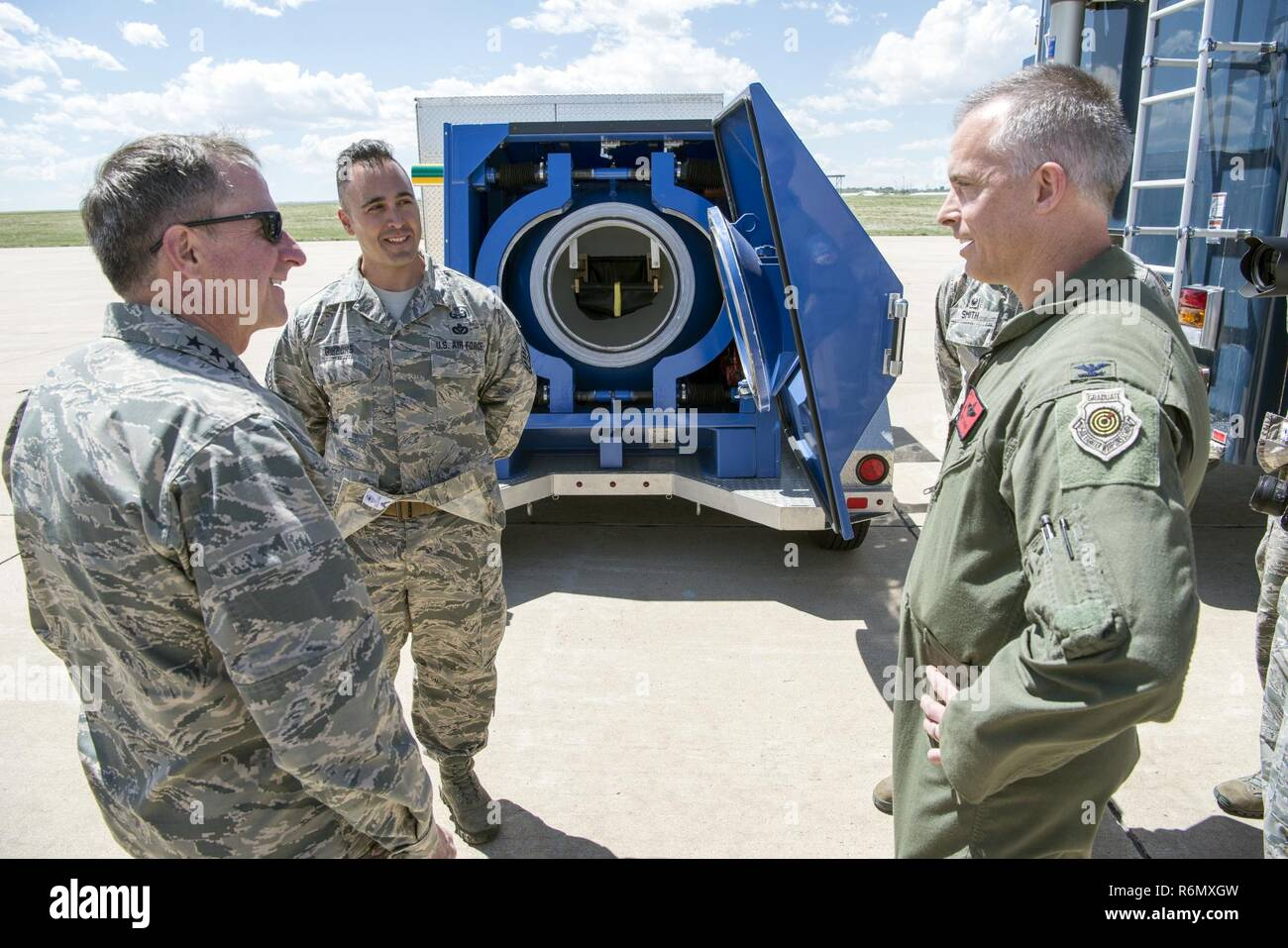 Colorado Air National Guard Senior Master Sgt. Richard F. Gibbons (center) stressed Explosive Ordinance Disposal mission engagement in the local area to U.S. Air Force Chief of Staff General David L. Goldfein. General Goldfein visited Buckley Air Force Base, Colo. and toured several static displays May 25, 2017. The 140th Wing, Colorado Air National Guard took the opportunity to showcase assets from their various missions to include the F-16C Fighting Falcon aircraft, the Mission Vehicle and Communications Vehicle from the 233d Space Group's Mobile Ground System, the 140th Explosive Ordnance D - Stock Image