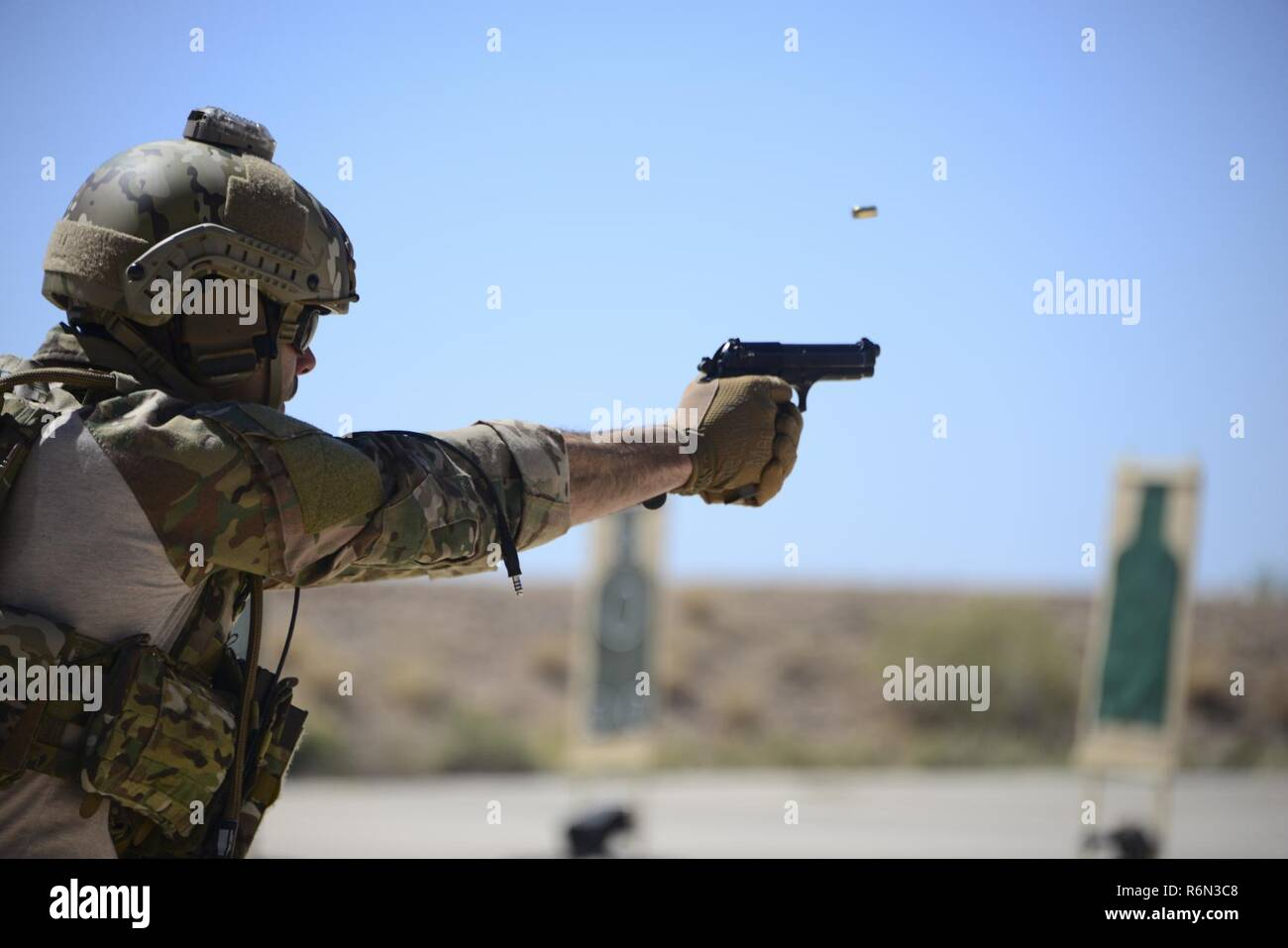 A U.S. Air Force pararescueman fires an M9 pistol at a target during the Guardian Angel Mission Qualification Training course at Davis-Monthan Air Force Base, Ariz., May 17, 2017. The MQT is a 90 day course that takes pararescuemen who have completed Air Education and Training Command schooling and helps them achieve their 5-level qualification. - Stock Image