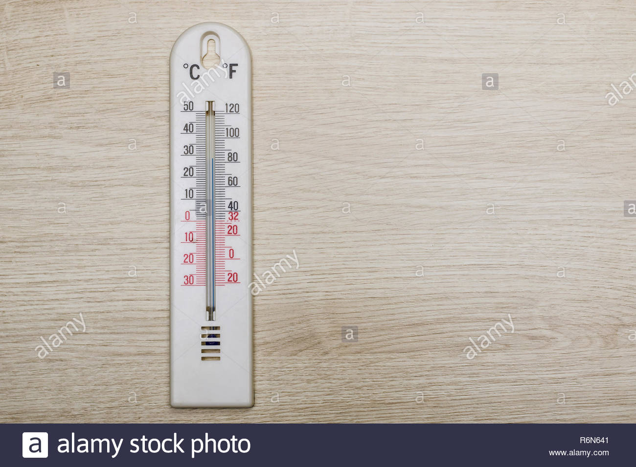 White room thermometer on wooden background - Stock Image