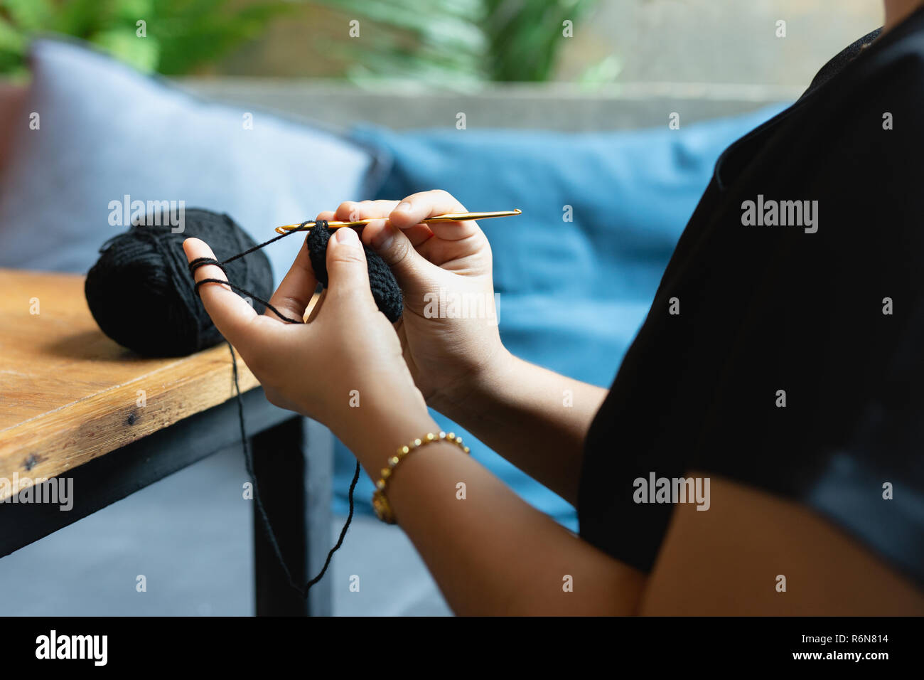Woman's hands knitting crochet relaxing at cafe. - Stock Image