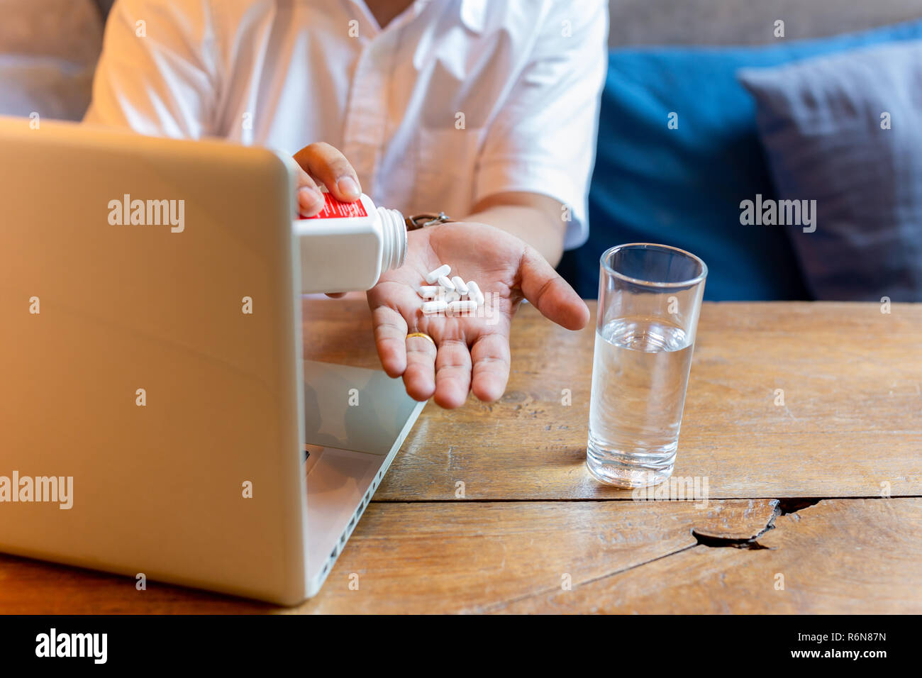 Man taking pill with glass of water and laptop on wooden table. - Stock Image